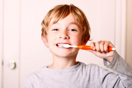 A boy brushing his teeth with an orange toothbrush.