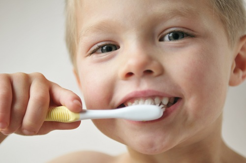 Little boy brushing teeth with white and yellow toothbrush